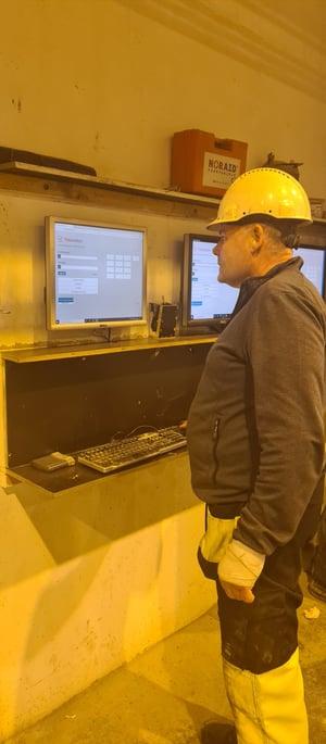Ansatte stempler seg inn på skjerm i produksjonslokalene